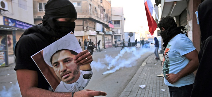 In this Jan. 3, 2015, file photo, a masked Bahraini anti-government protester holds a picture of jailed Shiite cleric Sheik Ali Salman, the head of the opposition al-Wefaq political association, as riot police fire tear gas canisters during clashes in Bil
