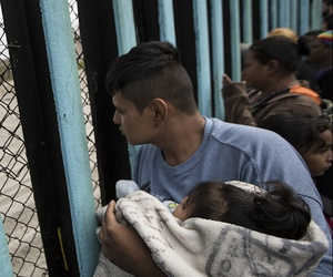A member of the Central American migrant caravan, holding a child, looks through the border wall toward a group of people gathered on the U.S. side, as he stands on the beach where the border wall ends in the ocean, in Tijuana, Mexico, April 29, 2018.