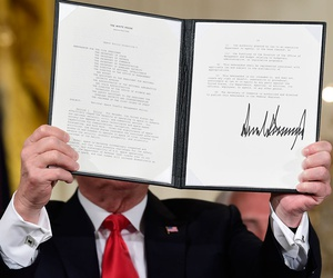 """President Donald Trump shows off a """"Space Policy Directive"""" after signing it during a meeting of the National Space Council"""