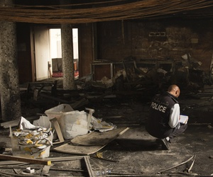 A police officer investigates damages at Libya's high national elections commission in Tripoli after a suicide bombing Wednesday, May 2, 2018.
