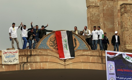 Mosul University students and activists place a national flag at the entrance of their university as they celebrate the liberation from Islamic State militants, on the eastern side of Mosul, Iraq, Sunday, Jan. 22, 2017.