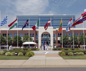 Guests and personnel from NATO's Allied Command Transformation participate in a U.S. Independence Day Flag Raising ceremony.