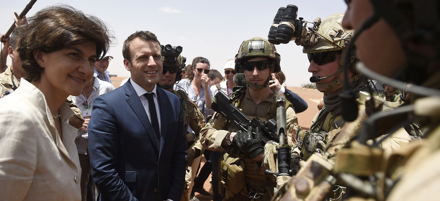 French President Emmanuel Macron, center, and Defense meet soldiers of Operation Barkhane, France's largest overseas military operation, in Gao, northern Mali, Friday, May 19, 2017.