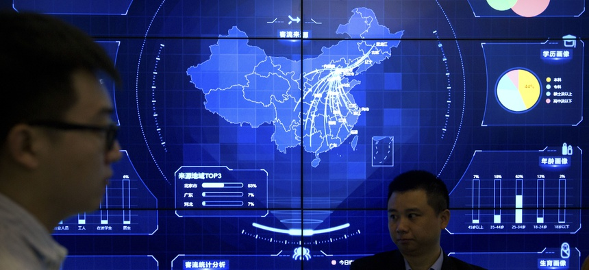 In this April 26, 2018, photo, visitors stand in front of an electronic data display showing a map of China at the Global Mobile Internet conference in Beijing.