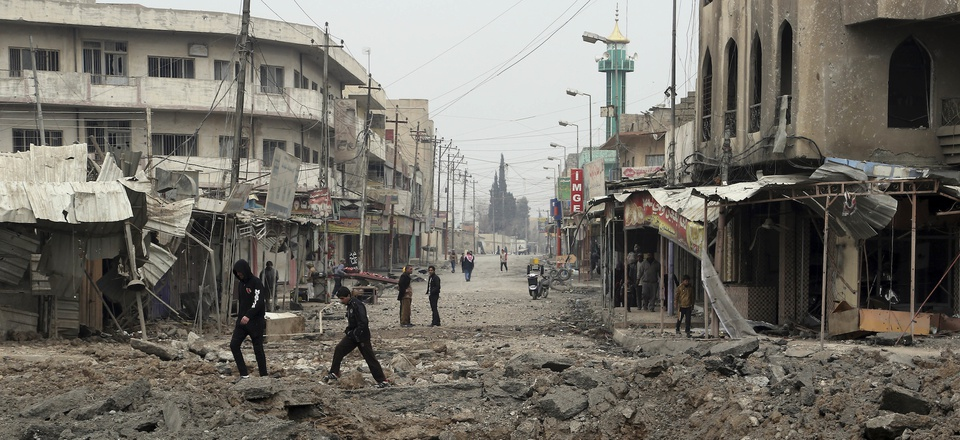 Civilians walk amid the rubble after fight between Iraqi security forces against Islamic State militants in the eastern side of Mosul, Iraq, Saturday, Jan. 21, 2017.