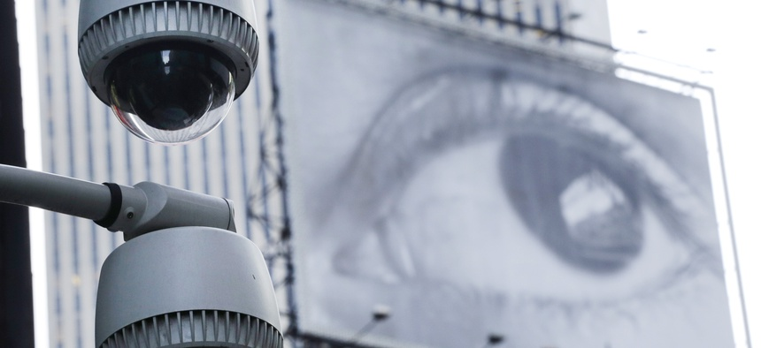 Security cameras are mounted on the side of a building overlooking an intersection in midtown Manhattan, Wednesday, July 31, 2013 in New York. In the background is a billboard of a human eye.