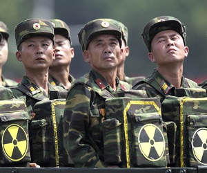 In this July 27, 2013 photo, North Korean soldiers turn and look towards their leader Kim Jong Un as they carry packs marked with the nuclear symbol during a ceremony marking the 60th anniversary of the Korean War armistice in Pyongyang, North Korea.