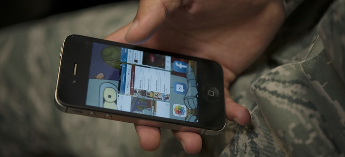 An airman scrolls through applications on a cellphone Jan. 31, 2014, at Incirlik Air Base, Turkey.