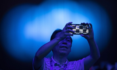 A spectator takes a cellphone photo of the CHAIN Cup at the China National Convention Center in Beijing, Saturday, June 30, 2018.
