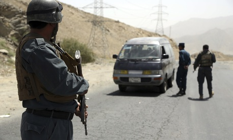 Afghan police officers search a vehicle at a checkpoint on the Ghazni highway, in Maidan Shar, west of Kabul, Afghanistan, Monday, Aug. 13, 2018.