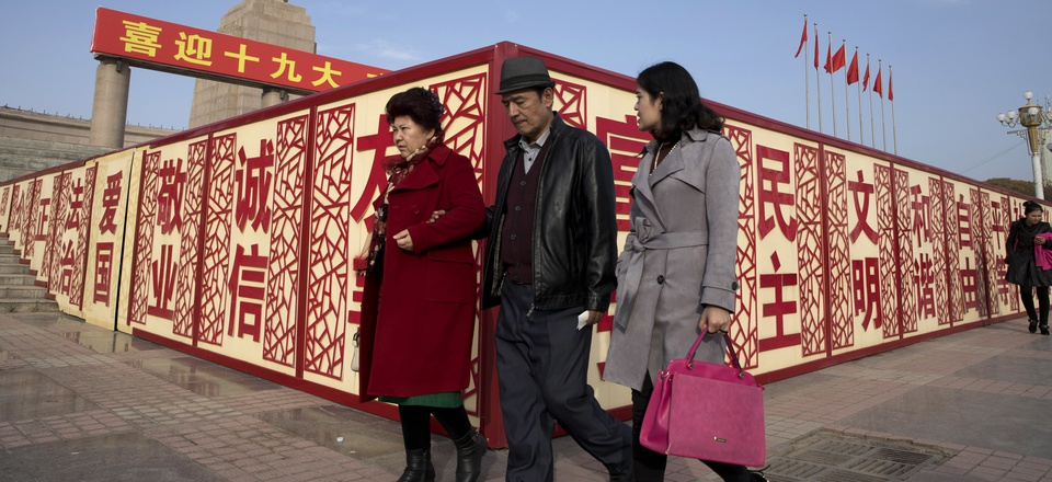 """In this Nov. 4, 2017 photo, residents walk past a statue showing Mao Zedong near billboards with the words for """"Welcome 19th Congress,"""" """"Patriotism"""" and """"Democracy"""" near a square in Kashgar in Xinjiang, China."""