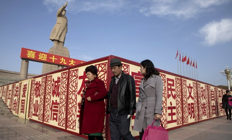 "In this Nov. 4, 2017 photo, residents walk past a statue showing Mao Zedong near billboards with the words for ""Welcome 19th Congress,"" ""Patriotism"" and ""Democracy"" near a square in Kashgar in Xinjiang, China."
