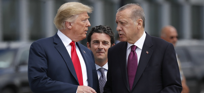 President Donald Trump, left, talks with Turkey's President Recep Tayyip Erdogan, right, as they arrive together for a family photo at a summit of heads of state and government at NATO headquarters in Brussels on Wednesday, July 11, 2018.