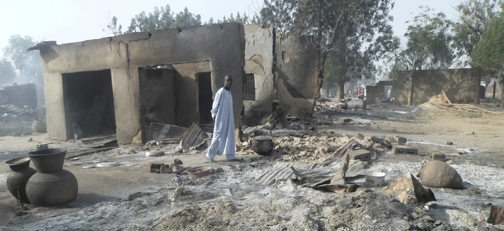 In this Sunday Jan. 31, 2016 file photo, a man walks past burnt out houses following an attack by Boko Haram in Dalori village near Maiduguri.