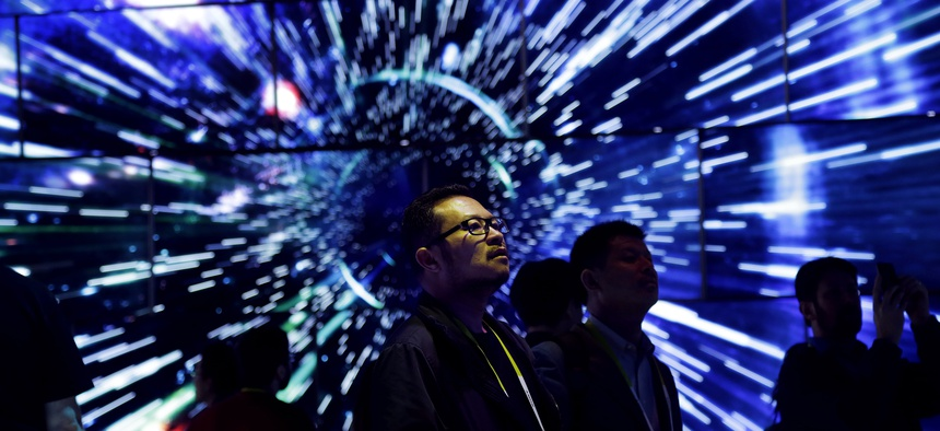 Bao Truong looks at a display of Samsung SUHD Quantum dot display TVs at the Samsung booth during CES International, Friday, Jan. 8, 2016, in Las Vegas
