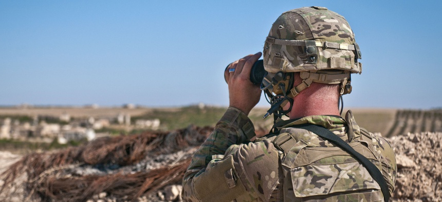 A U.S. soldier looks through binoculars to make visual contact with Turkish soldiers conducting a coordinated, independent patrol along the demarcation line near a village outside Manbij, Syria, July 16, 2018.