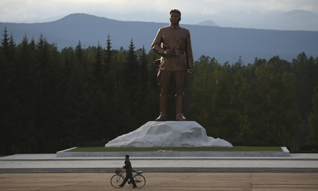 In this photo taken Friday, Aug. 17, 2018, a North Korean man pushes his bicycle past a monument to late North Korean leader Kim Il Sung at the Samjiyon Great Monument in Samjiyon, North Korea.