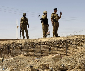 In this Friday, July 20, 2012 file photo, Iraqi soldiers patrol along the border between Syria and Iraq in Anbar province, Iraq.