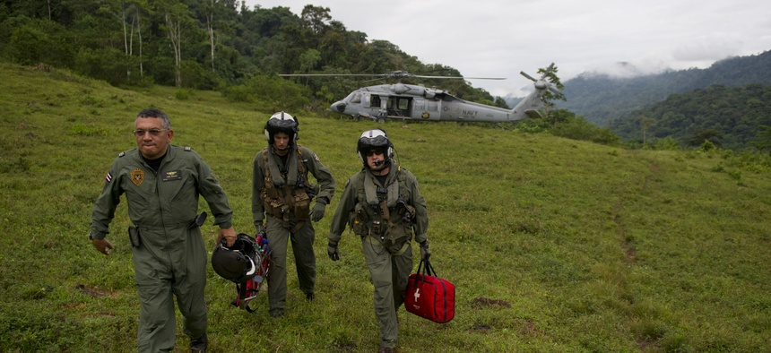 Costa Rica Police Air Patrol Officer Capt. George Lozano, left, Naval Air Crewman 3rd Class Joe Wainscott and Chief Naval Air Crewman Justin Crowe head toward a village to assist an injured boy in Bajo, Blay, Costa Rica, during Continuing Promise 2011.