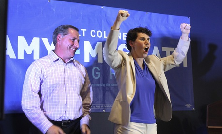 Amy McGrath, right, with her husband, Erik Henderson, pumps her fists after being elected as the Democratic candidate for Kentucky's 6th Congressional District, Tuesday, May 22, 2018, in Richmond, Ky.