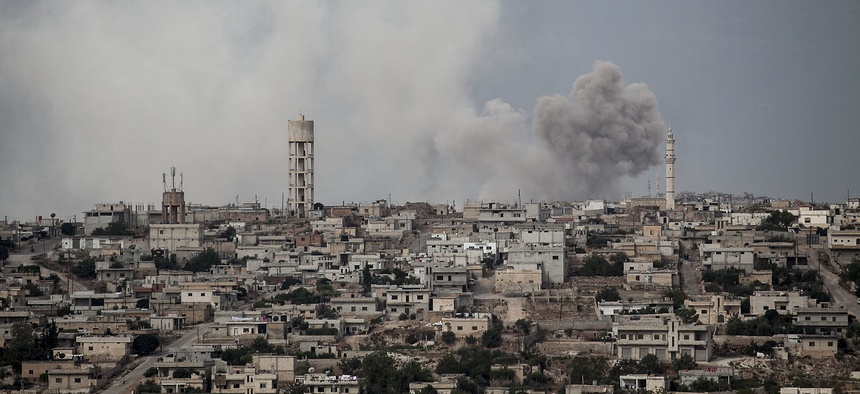 In this Sept. 19, 2013 photo, smoke rises after a TNT bomb was thrown from a helicopter, hitting a rebel position during heavy fighting between troops loyal to president Bashar Assad and opposition fighters, in the Idlib province countryside, Syria.
