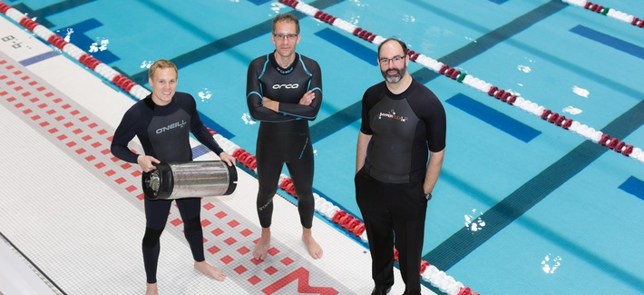 From left, graduate student Anton Cottrill, Dr. Jacopo Buongiorno and Dr. Michael Strano try out their neoprene wetsuits at a pool at MIT's athletic center. Cottrill is holding the pressure tank used to treat the wetsuits with heavy inert gasses.