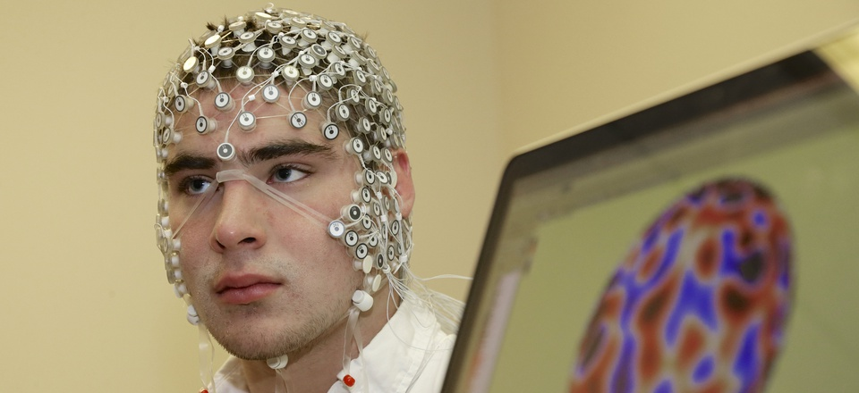 In this May 31, 2013, photo, research assistant Kevin Real wears an EEG net for detecting brain activity which is hooked up to a monitor, at the University of Nebraska's Center for Brain, Biology and Behavior in Lincoln, Neb.