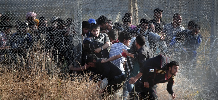 In this June 14, 2015  photo taken from the Turkish side of the border between Turkey and Syria, in southeastern Turkey, Syrian refugees burst into Turkey after breaking the border fence and crossing from Syria.