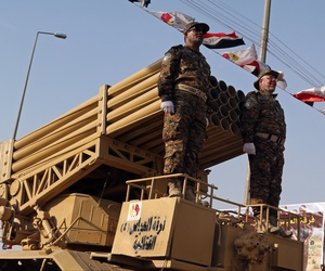 Members of the Abbas combat squad, a Shiite militia group, ride under militia and national flags atop a mobile rocket launcher during a military parade in Basra, 340 miles (550 kilometers) southeast of Baghdad, Iraq, Saturday, Sept. 26, 2015.