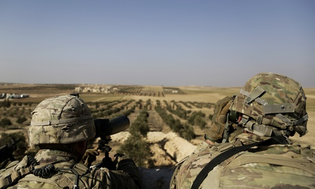 This Wednesday, Feb. 7, 2018 file photo, shows American troops looking toward the border with Turkey from a small outpost near the town of Manbij, northern Syria.