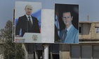 A local resident rides his motorcycle near portraits of Syrian President Bashar al-Asad, right, and Russian President Vladimir Putin in the town of Rastan, Syria, Wednesday, Aug. 15, 2018.