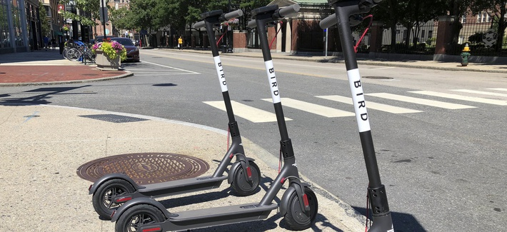 In this Friday, July 20, 2018 file photo, three dockless scooters stand on a sidewalk across the street from a Johnson & Wales University campus in downtown Providence, R.I.