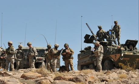 Soldiers from 4th Stryker Brigade Combat Team, 2nd Infantry Division and airmen from 5th Air Support Operations Squadron, along with observer-controllers, prepare for a Joint Air Attack Team exercise.