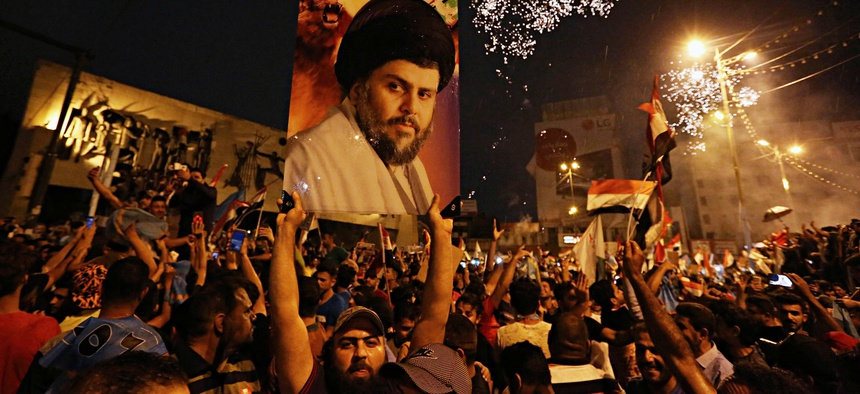 In this Monday, May 14, 2018 photo, supporters of Shiite cleric Muqtada al-Sadr, carry his image as they celebrate in Tahrir Square, Baghdad, Iraq.