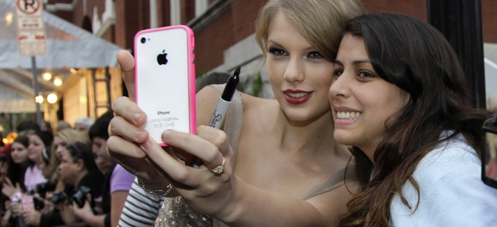 Country music star Taylor Swift helps Mariana Gomes, right, of Brazil, by taking a souvenir photo of them with Gomes' phone as Swift arrives for the Academy of Country Music Honors show on Monday, Sept. 19, 2011, in Nashville, Tenn.