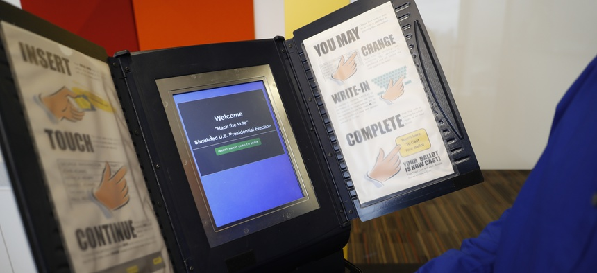 In this Wednesday, Sept. 28, 2016 photo, Brian Varner, a principal researcher at Symantec, inserts an identifying chip card into an electronic voting machine as he demonstrates how to hack an electronic voting machine at a Symantec office in New York.