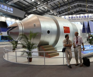 In this Nov. 16, 2010 file photo, visitors sit beside a model of China's Tiangong-1 space station at the 8th China International Aviation and Aerospace Exhibition in Zhuhai in southern China's Guangdong Province.