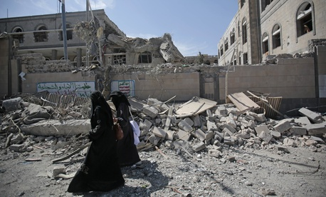 Yemenis walk past rubble after deadly airstrikes in and near the presidential compound, in Sanaa, Yemen, Monday, May. 7, 2018.