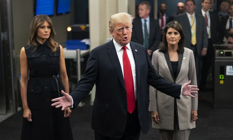 President Donald Trump addresses members of the news media as he arrives with First lady Melania Trump, left, and Nikki Haley, the U.S. ambassador to the United Nations, at U.N. headquarters, Sept. 25, 2018.