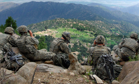 Soldiers from 2nd Battalion, 503rd Infantry Regiment, provide security during Operation Destined Strike while Soldiers below search a village in the Chowkay Valley in Kunar Province, Afghanistan.