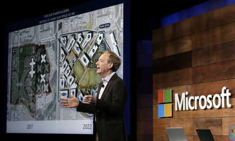 Microsoft president Brad Smith talks about the expansion of the company's headquarters, shown on a screen behind, at the annual Microsoft shareholders meeting, Wednesday, Nov. 29, 2017, in Bellevue, Wash.