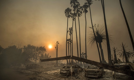 Smoke rises behind an apartment complex destroyed by fire in Ventura, California, December 5, 2017.