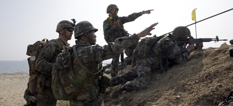 U.S. Marine, left, talks with South Korean Marines during the U.S.-South Korea joint landing military exercises south of Seoul, South Korea, Monday, March 30, 2015.