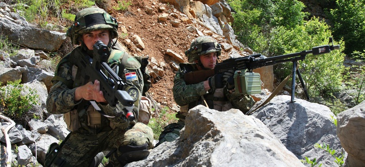 Two Croatian soldiers from 1st Platoon, 1st Company, Tiger Battalion, take cover and provide security as their platoon conducts a movement to contact exercise during the Immediate Response 2012 (IR12) training event held in Croatia on May 29, 2012.