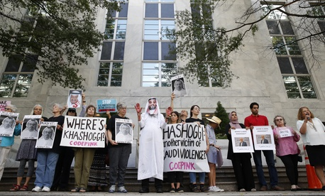 People hold signs at the Embassy of Saudi Arabia during protest about the disappearance of Saudi journalist Jamal Khashoggi, Wednesday, Oct. 10, 2018, in Washington.