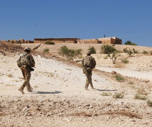U.S. Soldiers walk to a coordination point during an independent, coordinated patrol outside Manbij, Syria, August 19, 2018.