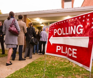 Voting polling place sign and people lined up on election day in 2008.