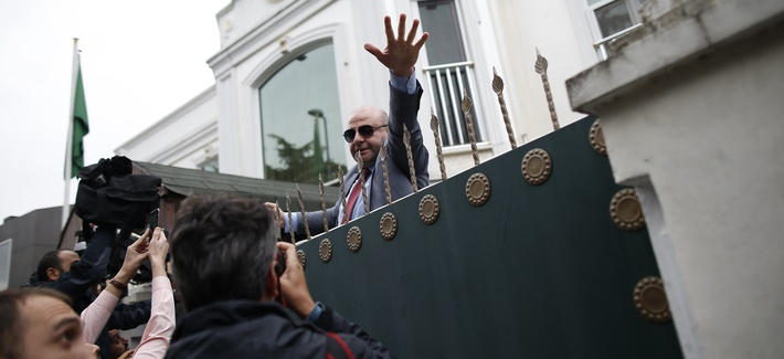 A security guard asks members of the media to back off, after rushing to cover the arrival of a group of a Saudi delegation that walked in the Saudi Arabia consul's residence in Istanbul, Wednesday, Oct. 17, 2018.