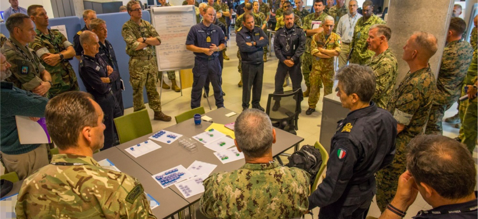 Participants of the Amphibious Leaders Expeditionary Symposium (ALES) gather around to discuss interoperability at NATO Joint Warfare Center in Stavanger, Norway, June 20, 2018.