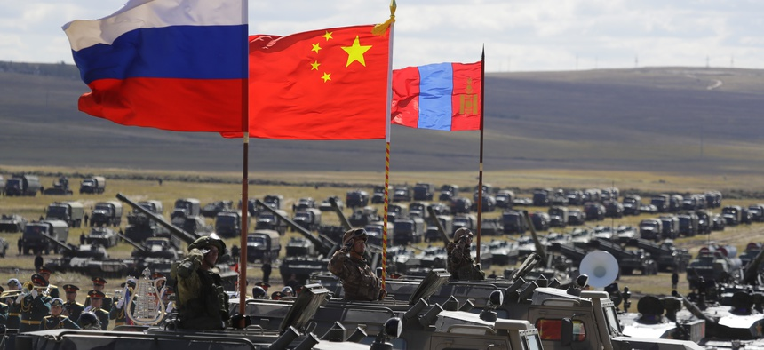 """Russian, Chinese and Mongolian national flags set on armored vehicles develop in the wind during a military exercises on training ground """"Tsugol"""", during the military exercises Vostok 2018 in Eastern Siberia, Russia, Sept. 13, 2018."""
